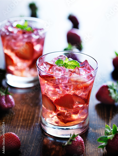 Fototapeta cocktail with strawberries, ice, and mint