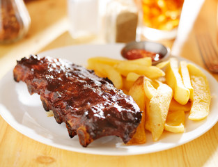 plate with barbecue ribs and french fries