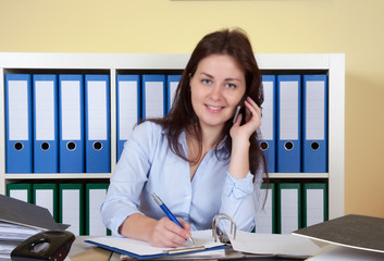 Laughing woman at office talking at phone
