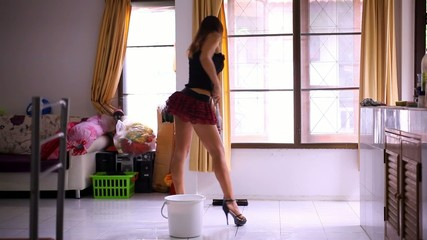 Beautiful young sexy maid cleans tiled floor, concept cleaning.