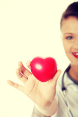 Young female doctor with heart in her hand