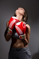 Girl with boxing gloves in front, opening the neck