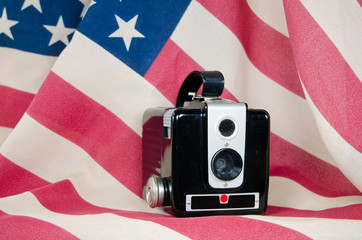old-fashioned camera on American flag