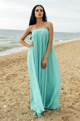 sexy beautiful woman in elegant dress posing at beach