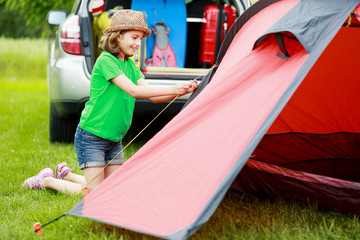 Camp in the tent -  girl setting a tent on the camping