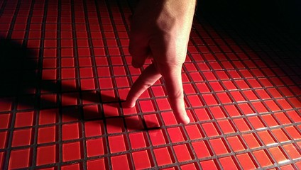 Walking hand on red tiling wall