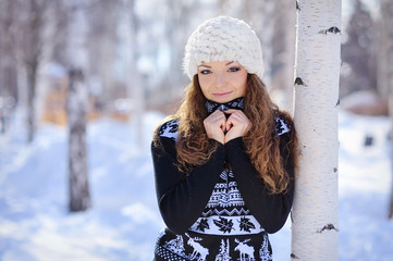 beautiful girl in white hat stands near the birch in winter