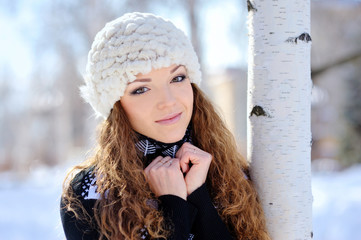 beautiful girl stands near the birch in winter