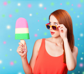 Redhead girl with toy ice cream on blue background.