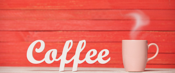 Abstract wooden word Coffee with cup on red wooden background.
