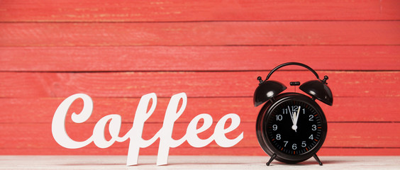 Alarm clock and wooden word Coffee.