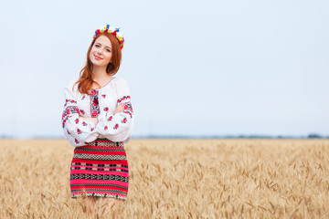Redhead girl in national ukrainian clothes on the wheat field.