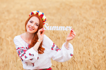Redhead girl in national ukrainian clothes with wooden word Summ