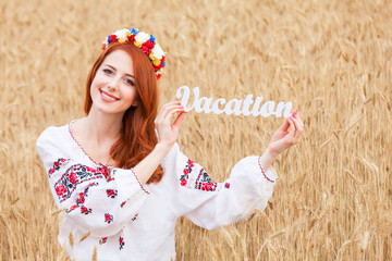 Redhead girl in national ukrainian clothes with wooden word Vaca