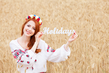 Redhead girl in national ukrainian clothes with wooden word Holi