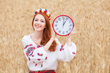 Redhead girl in national ukrainian clothes with clock on the whe