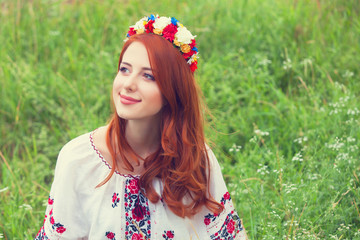 Redhead girl in nationac ukrainian clothes on the green grass.