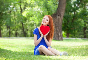 Redhead girl with heart shape in the park.