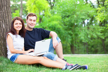 Teen couple with gift in the park.