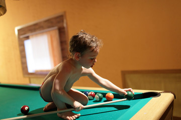 Child sitting on the pool table