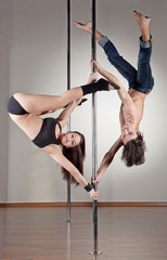 Young couple of pole dancers stopped in acrobatic position on th
