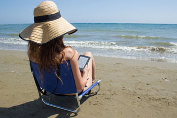 girl on the beach with ebook reader