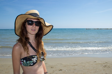 girl with sunglasses and hat on the beach