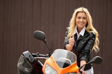 Junge Motorradfahrerin mit Daumen nach oben