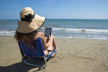 a girl reading ebook on a chair on the beach