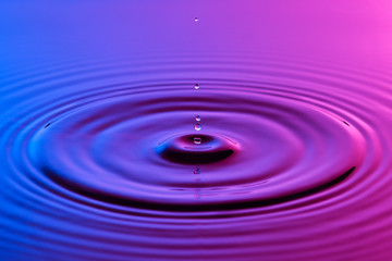 Water drop close up with concentric ripples colourful blue and p