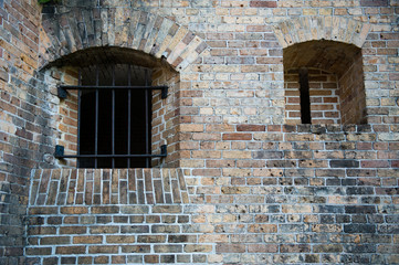Iron bars, gun slot in brick wall