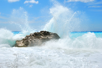 Big sea wave breaking on the shore rocks with a high sea spray