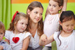 Woman as child care worker in kindergarten
