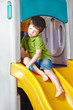Boy playing on slide in kindergarten