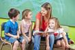 Child care worker and children reading book in kindergarten
