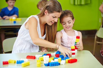 Nursery teacher and girl playing with building bricks