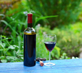 Bottle of wine with corkscrew and glass in the garden