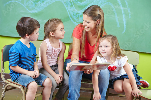 Child care worker and children reading book in kindergarten