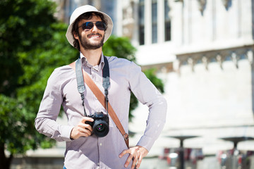 Happy tourist holding a camera