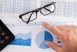Calculator, eyeglasses and financial charts