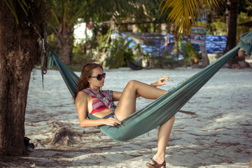 woman in sunglasses lying at hammock by the beach. Koh Phangan