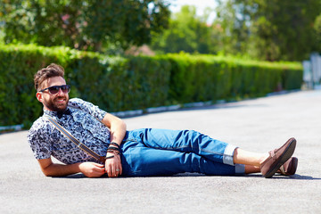 cheerful young adult man lying on the road