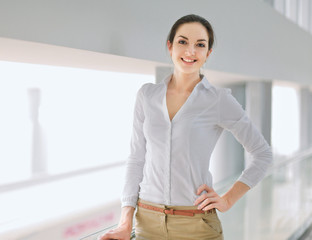 Portrait of a happy young business woman standing, isolated on