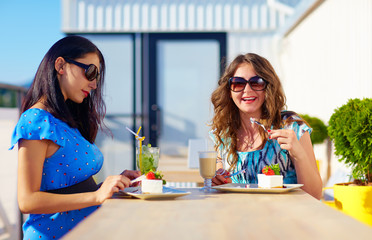 happy female friends enjoying cakes in cafe, pregnant women
