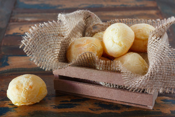 Brazilian snack cheese bread (pao de queijo)  in wooden box with