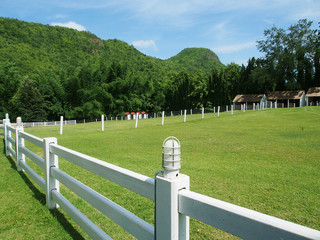 County style white fence in farm field