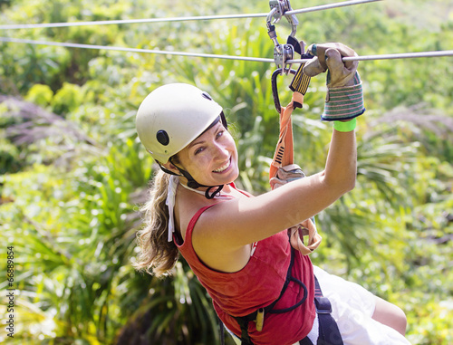Woman going on a jungle zip line adventure - 66889854
