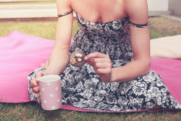 Young woman having tea outside