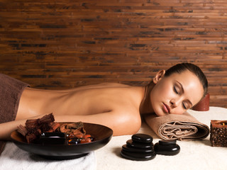 Beautiful young woman relaxing in the spa salon.