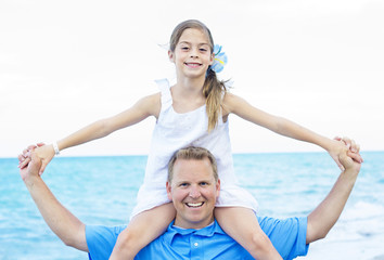 Daughter sitting on Fathers Shoulders at the Beach